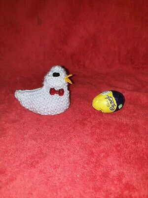 Hand knitted Easter chick egg cosy to cover a creme egg. Red glitter bow