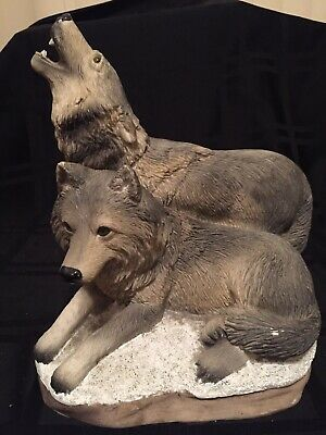 Statue Of Wolves In Snow Howling And At Rest On A Rock
