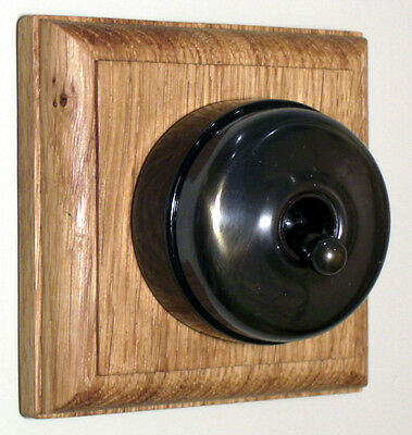 Period Single Oak Pattress with Plain Antique Brass Black Ceramic Dolly Switch