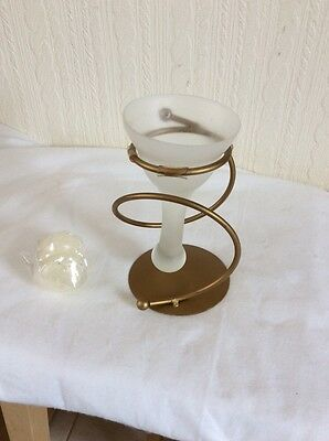 A Gold Stand With A Frosted Glass Droplet Holder