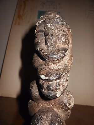 early ivory coast effigy  of a man carring something on his back