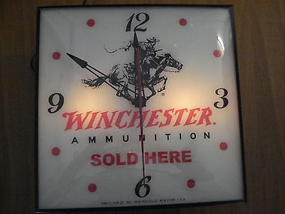 "Vintage Pam lighted clock advertising ""Winchester ammunition sold here""."