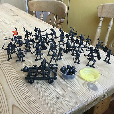 34 black plastic knight figures in battle pose + cannon ball firer, balls, flag