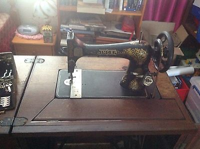 antique Singer treadle sewing machine in a wooden cabinet