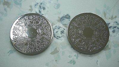 Pair of silver colored 9.5cm diameter metal coasters with engraved pattern