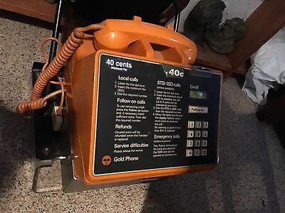 Old orange Gold Pay Phone complete with dome