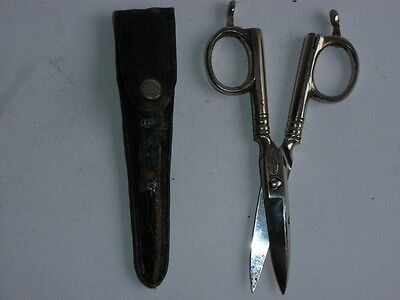 Vintage metal scissors - needle bed with leather cover .