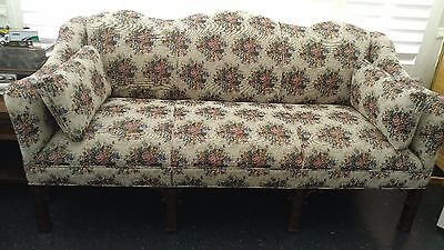 camelback loveseat with decorative wood work, upholstery fabric