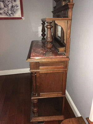 Antique oak buffet with marble top and small mirror on backboard.
