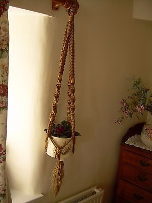 Hanging Macrame plant holder with big wooden beads. Very retro.