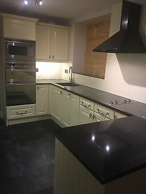Used cream kitchen with black quartz worktop and appliances