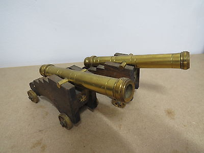 2x vintage brass cannons on wooden carriage