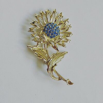 vintage gold tone flower brooch decorated with blue rhinestones