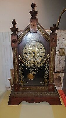unmarked wooden mantel wind-up clock with key