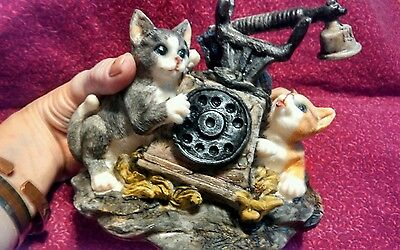 Cats playing with large phone figurine