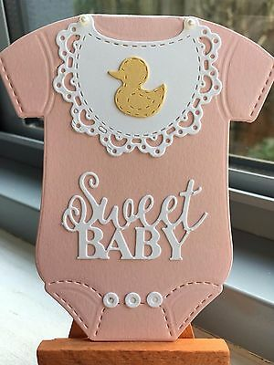 Handmade baby girl card in stand-up, jumpsuit/bodysuit design. Light pink.