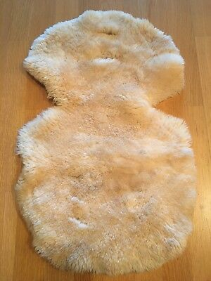 Sheepskin buggy or car seat liner for baby. multiple openings for adjustable fit