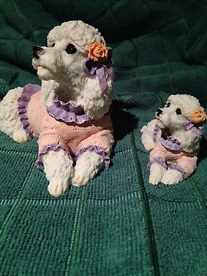 Poodle dogs. Two ceramic sculptures of white poodles with pink shirts.
