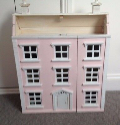 Classic four storey wooden dolls house with some furniture.