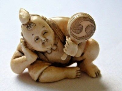 Japanese netsuke of Karakao Boy resting with toy in his hand playing