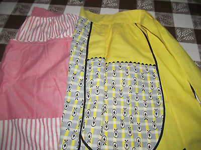 Two vintage handmade half aprons. One yellow w/black & one pink.
