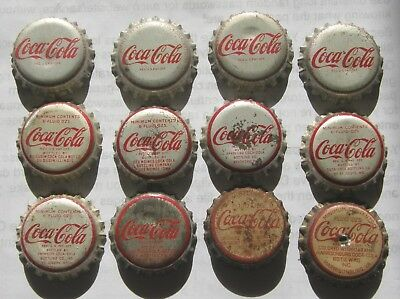 Dozen different cork-lined Coca-Cola soda bottle caps with cities on the faces