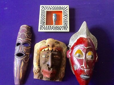 Three wooden masks plus small masks in frame.