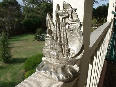 Artist impressed stainless steel flagship ornament. 17 cm x 12 cm. Very heavy.