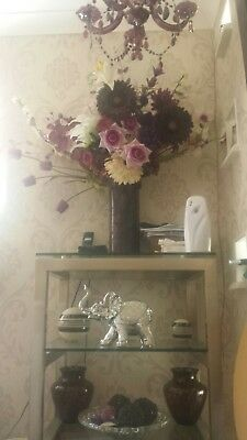 Large purple vase with a large amount of silk flowers