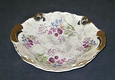 Vintage porcelain pierced candy dish with gold trim. Colorful daisy artwork