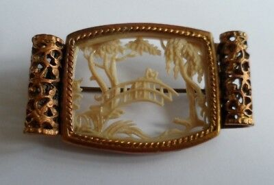 Antique/vintage brooch with a tiny pierced carving of a bridge, trees etc.