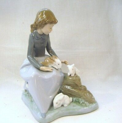 LLADRO/NAO Pretty young Girl feeding three Rabbits she is sitting on a log
