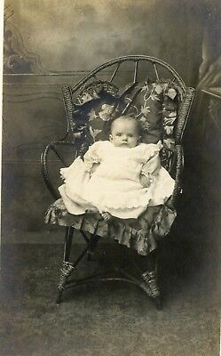 Studio portrait of young baby with toes poking out of gown by Ross