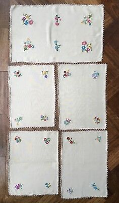 Four hand embroidered placemats and a tea tray cloth mat vintage 1950s