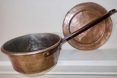 antique copper pot with blacksmith wrought iron handle and a hand hammered plate