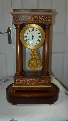 Portico clock the style of 19th century French Empire The wood has a floral inla