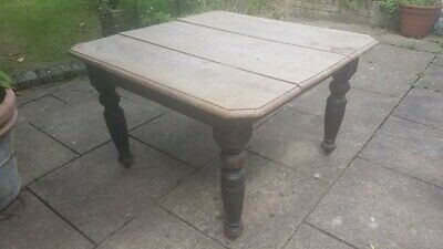 edwardian solid oak dining table with extra leaf and winder.