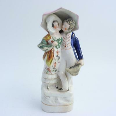 19th CENTURY STAFFORDSHIRE POTTERY FIGURE OF A KISSING COUPLE UNDER UMBRELLA