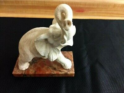 MC white alabaster hand carved elephant on marble base.
