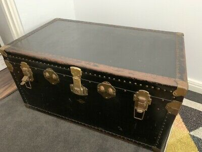 Antique black travel chest with latches and leather side handles