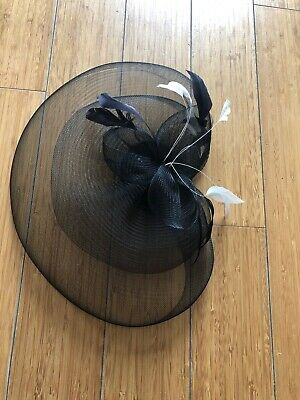 Black petalled fascinator on comb, with white and black feathers, worn once, vgc