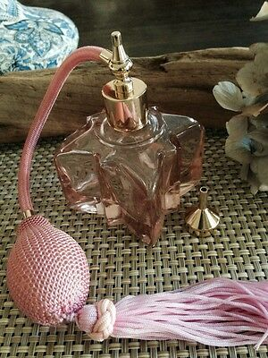 A new art  deco perfume bottle atomizer with pink tassel in pink clear glass
