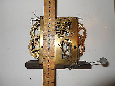 Antique american clock movement on the wooden base
