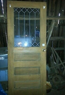 Antique 1860s exterior wooden farmhouse door with lead glass design, small crack