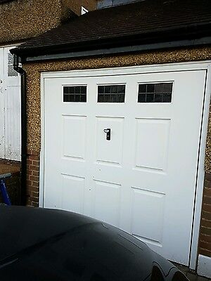 White up and over garage door including frame with windows