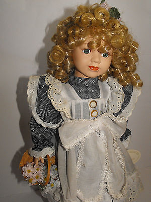 Beautiful porcelain doll is holding a basket with flowers