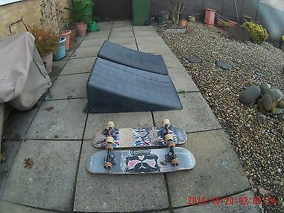two skate ramps with 2 used skateboards