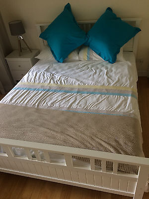 White Queen bed frame and mattress with matching bedside cabinets.