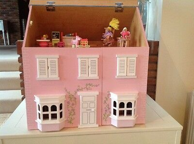 Wooden Dolls House with furniture and dolls.
