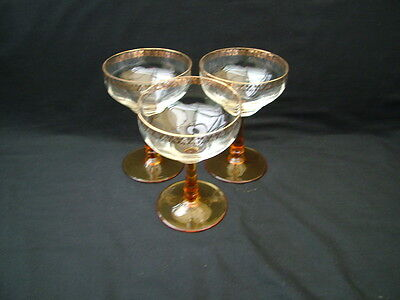 Set of 3 coupe shape wine glasses with gold leaf motif rim and amber stem